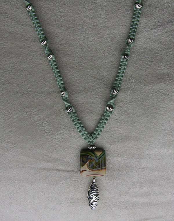 Green Macrame Necklace With Ceramic Focal Bead And Silver Coloured Pendant